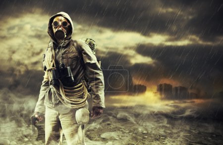 Photo for A lonely hero wearing gas mask, city destroyed on the background - Royalty Free Image