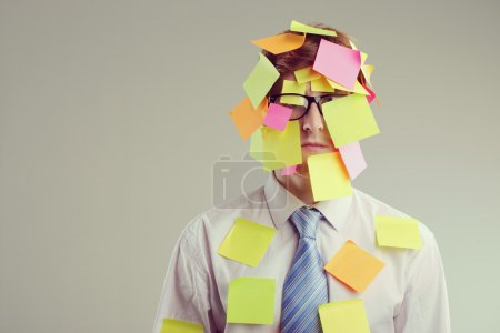 Photo for Office worker with post-its all over his face - Royalty Free Image