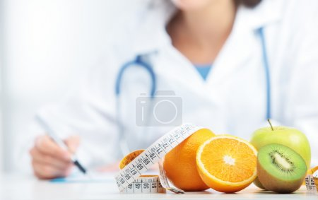 Photo for Nutritionist Doctor is writing a prescription. Focus on fruit - Royalty Free Image