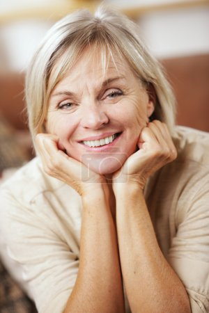 Photo for Portrait of a smiling senior woman sitting on couch - Royalty Free Image