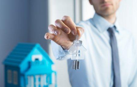 Photo pour Agence immobilière donnant les clés de la maison avec maison modèle sur fond. - image libre de droit