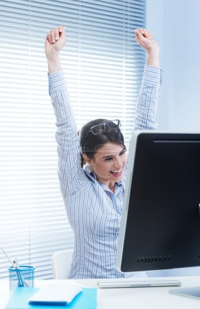 Photo for Young joyful woman at desk with fists raised receiving good news. - Royalty Free Image