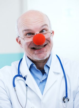 Photo for Funny senior doctor with red clown nose and funny expression. - Royalty Free Image
