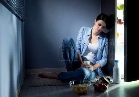 Photo for Sleepless sad woman sitting on kitchen floor having a glass of milk. - Royalty Free Image