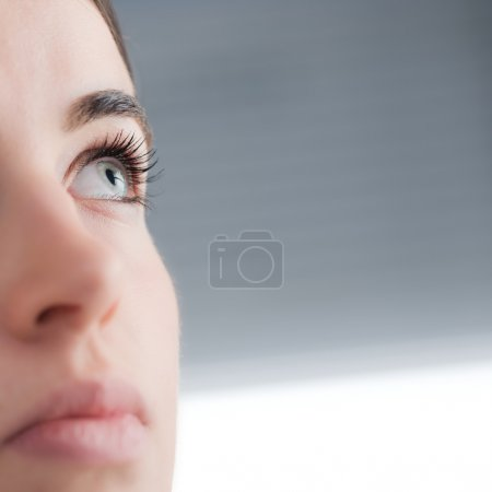 Photo for Young attractive blue eyed woman thinking close up. - Royalty Free Image
