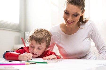 Photo pour Mère et super-héros enfant jouant et réunissant dans le salon. - image libre de droit