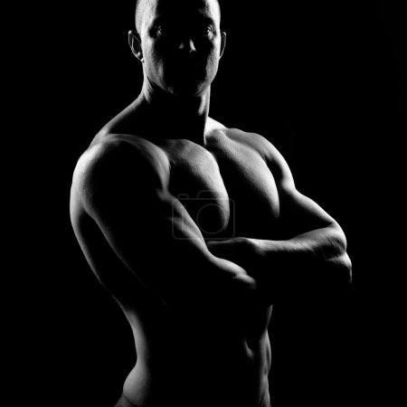 Photo for Attractive body builder posing and showing off muscles on dark background. - Royalty Free Image
