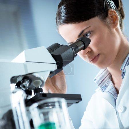 Female researcher using microscope