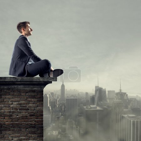 Businessman sitting on top of a building looking f...