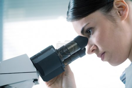 Female researcher using microscope