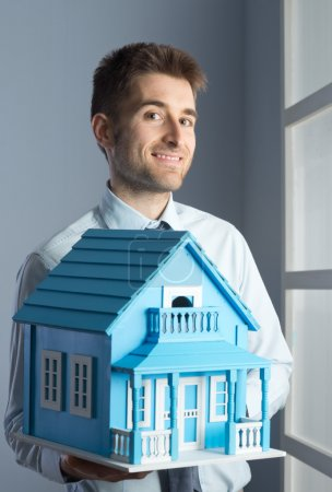 Photo for Friendly real estate agent with light blue model house. - Royalty Free Image