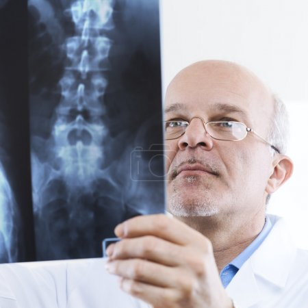 Male senior doctor looking at x-ray images of human spine.