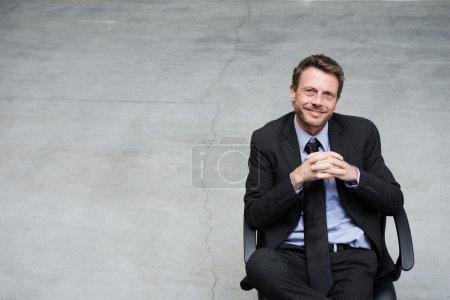 Photo pour Homme d'affaires souriant assis sur une chaise de bureau avec les mains jointes sur le fond de sol en béton . - image libre de droit