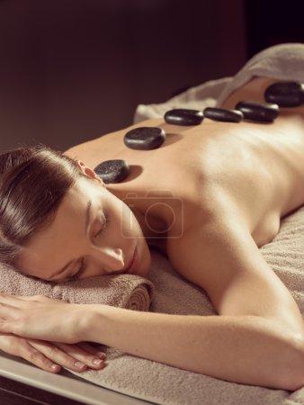 Photo pour Jeune femme recevant une thérapie de massage aux pierres chaudes au spa . - image libre de droit