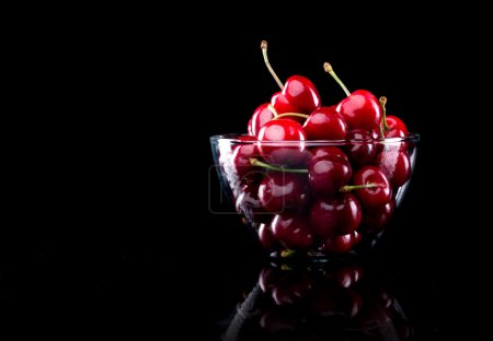 Photo for Juicy shiny cherries in a glass bowl on black background. - Royalty Free Image