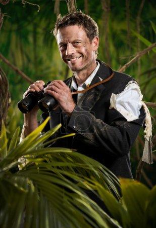 Confident businessman holding binoculars and exploring jungle.
