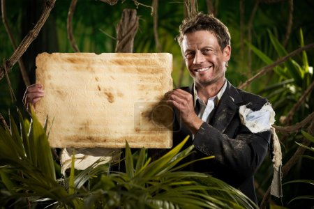 Photo pour Homme d'affaires souriant dans la jungle tenant un vieux parchemin taché . - image libre de droit