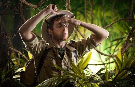 Photo pour Fatigué jeune explorateur dans la jungle essuyant la sueur de son front . - image libre de droit