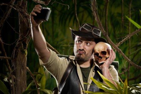 Photo pour Jeune aventurier prenant un autoportrait avec un crâne dans la jungle . - image libre de droit