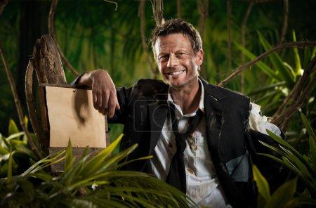 Photo pour Homme d'affaires survivant penché vers un vieux panneau dans la jungle et souriant à la caméra . - image libre de droit