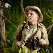 Explorer walking in jungle being watched by a secu...