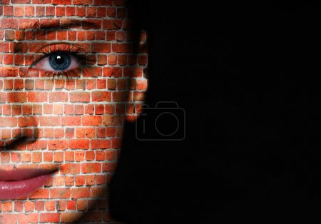 Photo for Woman face covered with brick wall pattern over black background - Royalty Free Image