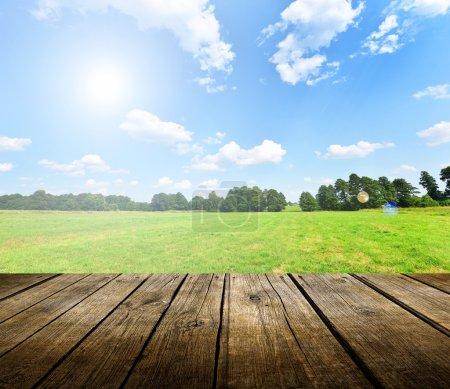 Photo pour Table de terrasse en bois vide avec ciel bleu en arrière-plan. Prêt pour le montage d'affichage du produit . - image libre de droit