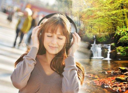 Photo pour Femme écoutant de la musique relaxante dans la ville et se téléporter à la belle forêt avec cascade - image libre de droit