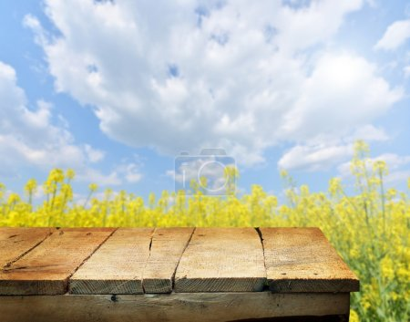 Empty wooden deck table with spring flowers in bac...