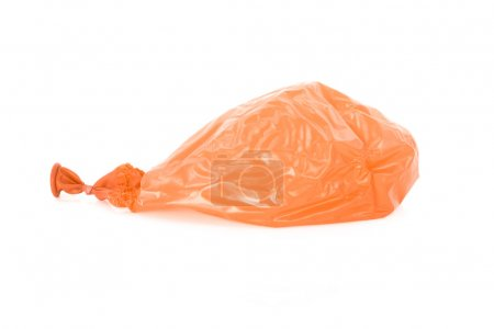 Deflated orange balloon isolated over white