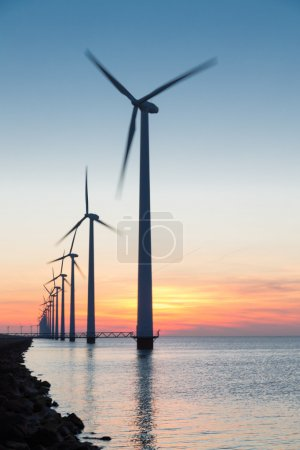 Dutch row offshore wind turbines at beautiful sunset