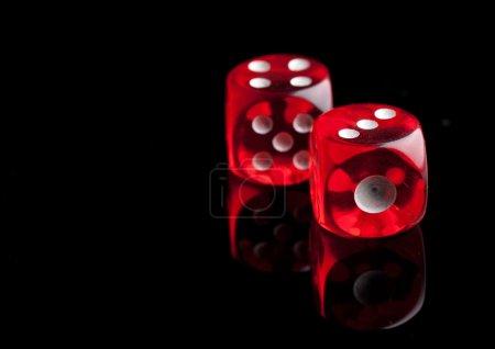 Photo pour Deux dés rouges sur fond noir - image libre de droit
