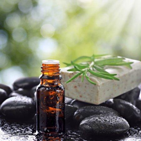 Photo pour Flacon d'aromathérapie, savonnette, pierres noires humides et bokeh naturel en arrière-plan - image libre de droit