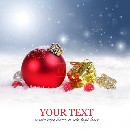 Photo for Christmas background with a red ornament and golden gift box with snowflakes falling from a clear blue sky - Royalty Free Image