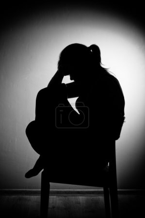 Photo for Sad woman sitting alone in a empty room - black and white - Royalty Free Image