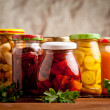 Composition with jars of pickled vegetables. Marin...