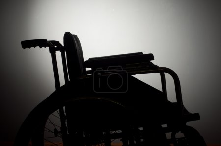 Closeup empty wheelchair on dark background and shadow