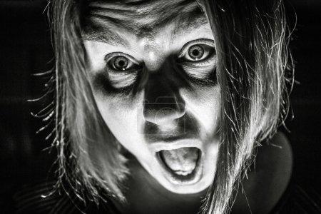 Photo pour Une femme regarde la peur de la mort, comme si elle hurle au secours. - image libre de droit