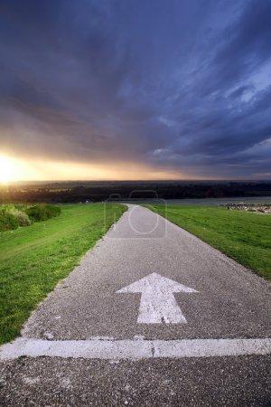 Photo pour Route goudronnée avec flèche et coucher de soleil en arrière-plan - image libre de droit