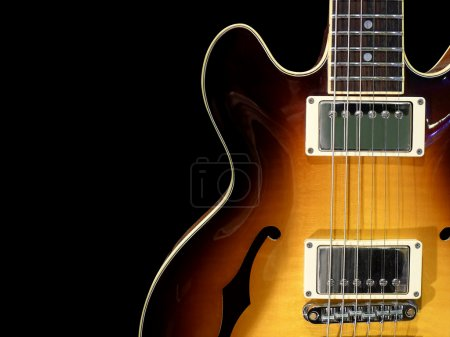 Photo for Close-up of vintage semi acoustic electric jazz guitar on black background. - Royalty Free Image