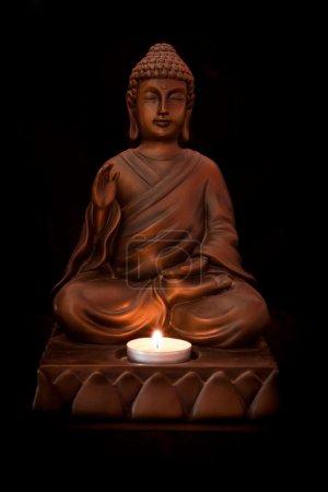 Photo pour Statue de Bouddha avec une bougie sur fond noir - image libre de droit