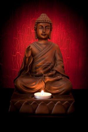 Photo pour Statue de Bouddha avec une bougie sur un fond rouge - image libre de droit
