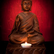 Buddha statue with a candle on a red background...