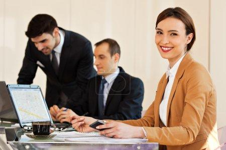 Photo pour Jeune belle femme d'affaires souriant avec des collègues hommes d'affaires en arrière-plan regardant leurs écrans d'ordinateur portable - image libre de droit