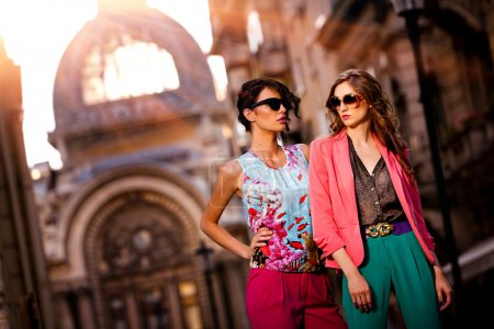 Photo for Fashion shot of two elegant beautiful girls in the sunset wearing sunglasses. Two young women outdoor on the street. Shopping inspiration - Royalty Free Image