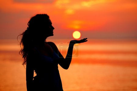 Photo for Happy free Woman enjoying in Sea Sunset. Silhouetted against the sunset, sunrise. Sun on the palm - Royalty Free Image