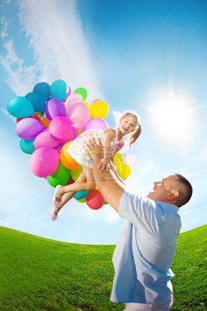 Photo for Father throws daughter. Familly playing together in park with balloons. Father tosses a baby against the sky - Royalty Free Image
