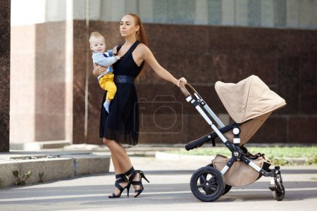 Trendy modern mother on a city street with a pram. Young mother