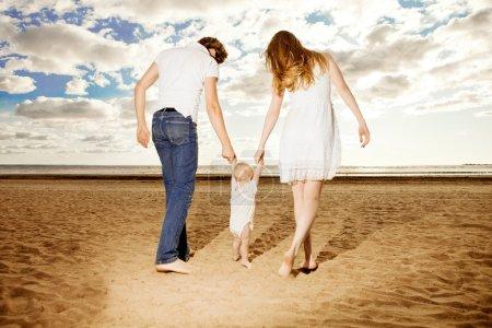 Photo pour Premiers pas du gamin. Une famille heureuse aide bébé à faire ses premiers pas sur la plage - image libre de droit