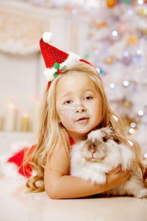 Beautiful little Santa girl near the Christmas tree.  Happy girl